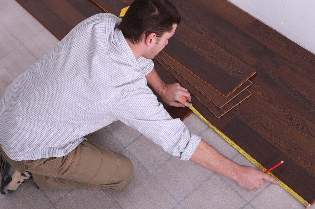 man measuring the wood planks